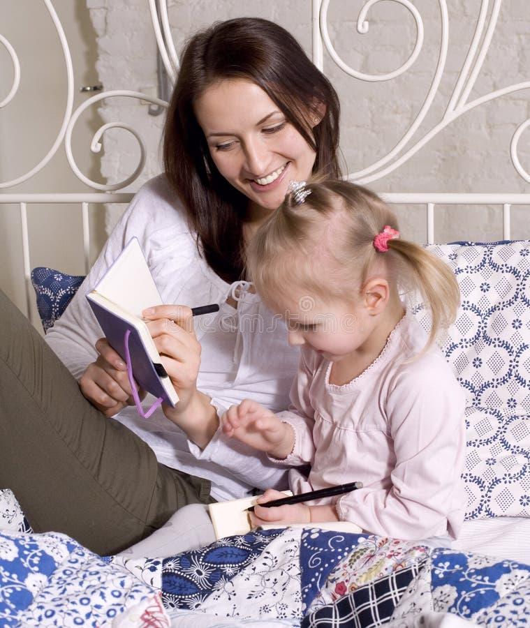 Retrato da família, da mãe e da filha felizes na cama imagens de stock