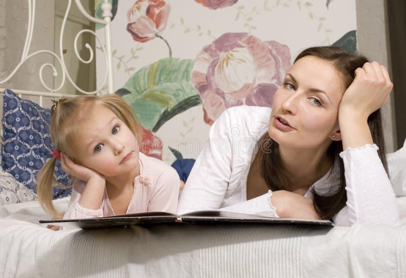Retrato da família, da mãe e da filha felizes na cama foto de stock