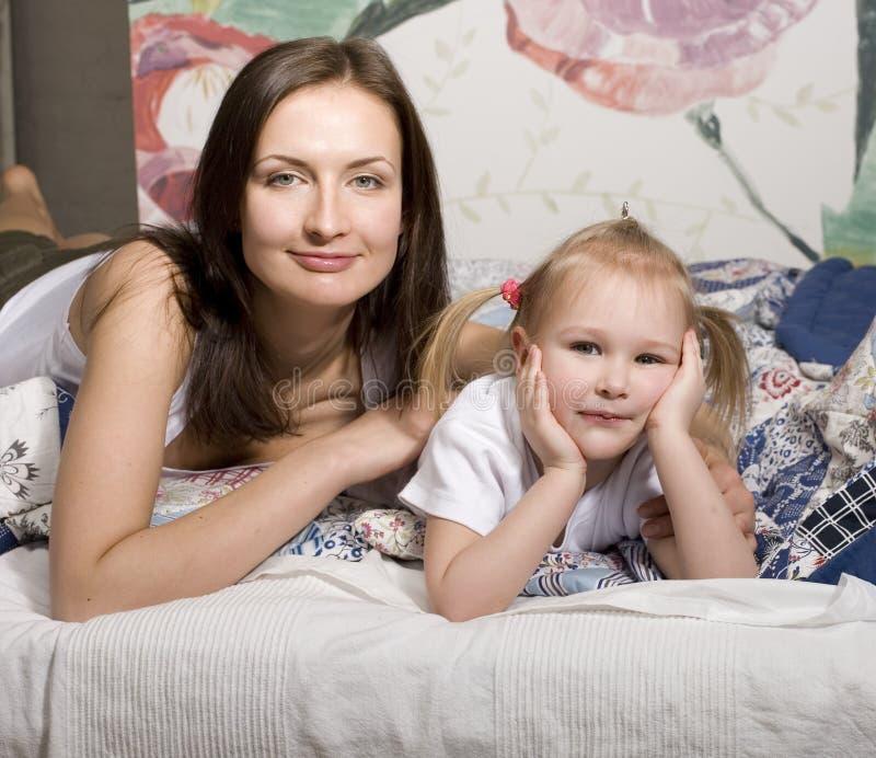 Retrato da família, da mãe e da filha felizes na cama foto de stock royalty free