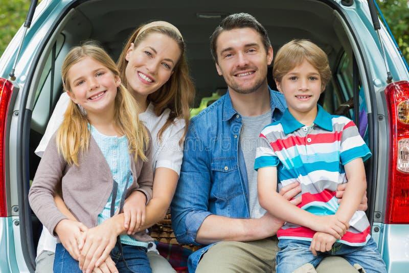 Retrato da família de quatro pessoas feliz que senta-se no tronco de carro imagem de stock