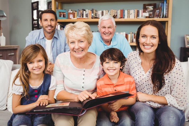 Retrato da família de sorriso com as avós que guardam o álbum de fotografias foto de stock