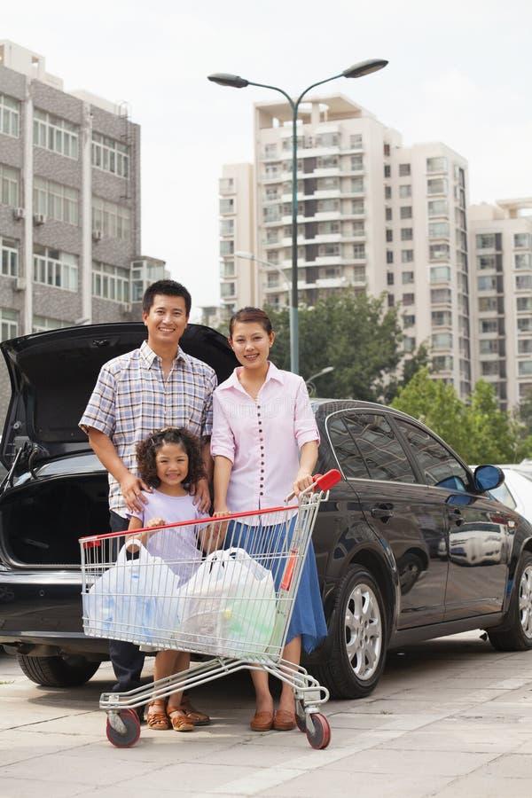 Retrato da família de sorriso com o carrinho de compras que está ao lado do carro, fora foto de stock