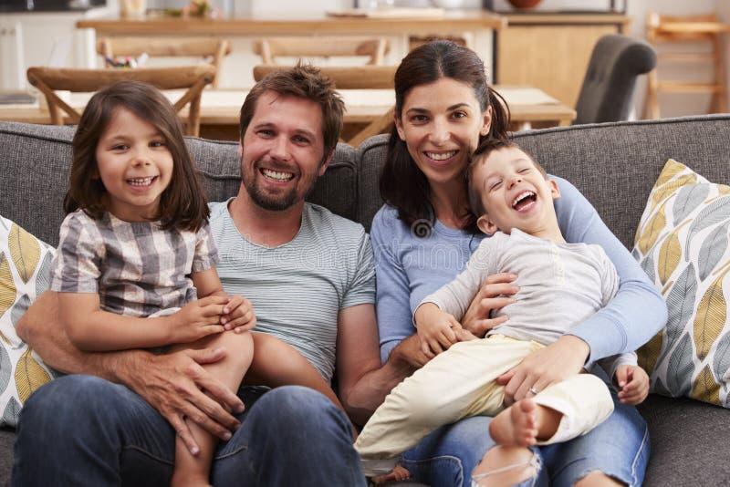 Retrato da família de sorriso que senta-se no sofá em casa imagem de stock royalty free