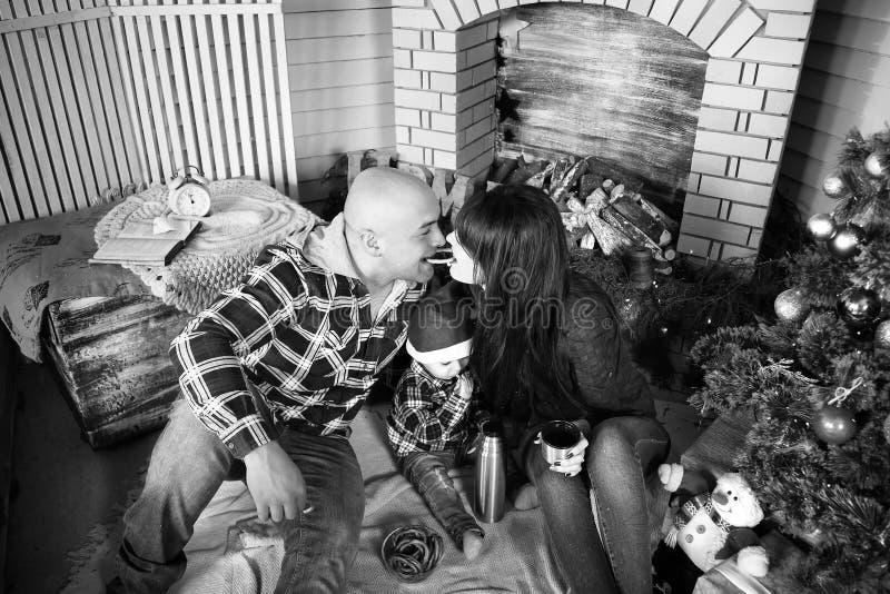 Retrato da família do Natal de pais felizes novos com a criança pequena no chapéu vermelho de Santa perto de comer da árvore e da imagens de stock royalty free