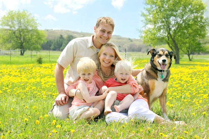 Retrato da família e do cão felizes no prado da flor imagens de stock royalty free