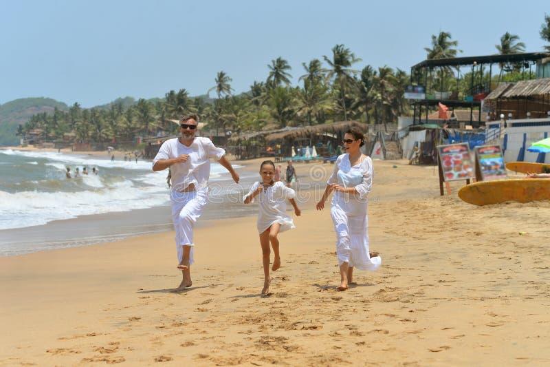 Retrato da família feliz bonito que corre no Sandy Beach fotografia de stock royalty free