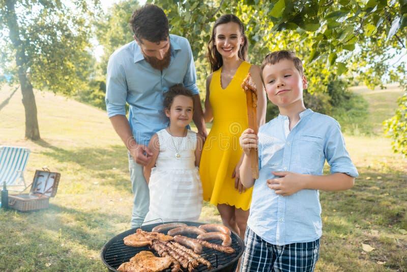 Retrato da família feliz com as duas crianças que estão fora perto de um assado fotos de stock