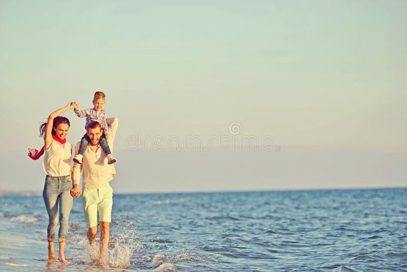 Retrato da família feliz e do bebê que apreciam o por do sol no lazer do verão foto de stock royalty free
