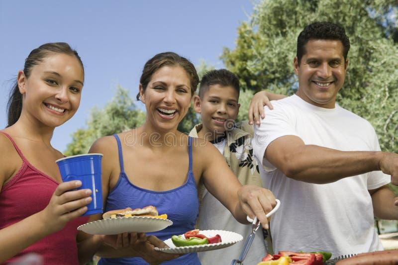 Retrato da família feliz em torno da grade no piquenique fotos de stock royalty free