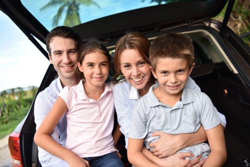Retrato da família feliz em um tronco de carro foto de stock