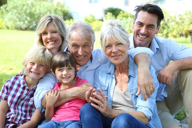 Retrato da família feliz grande que senta-se na grama imagens de stock royalty free