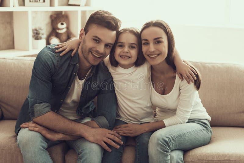 Retrato da família feliz nova que senta-se no sofá foto de stock