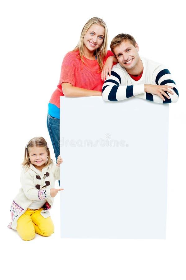 Retrato da família feliz que apresenta o whiteboard imagens de stock royalty free