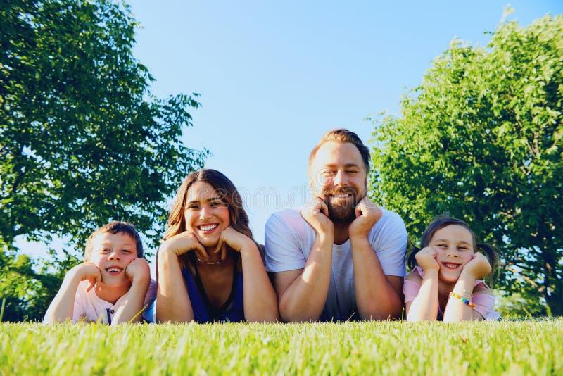 Retrato da família feliz que encontra-se junto no gramado foto de stock royalty free