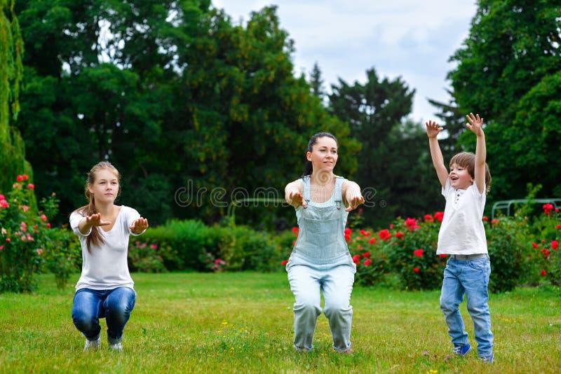 Retrato da família feliz que faz o exame e os esportes fotografia de stock