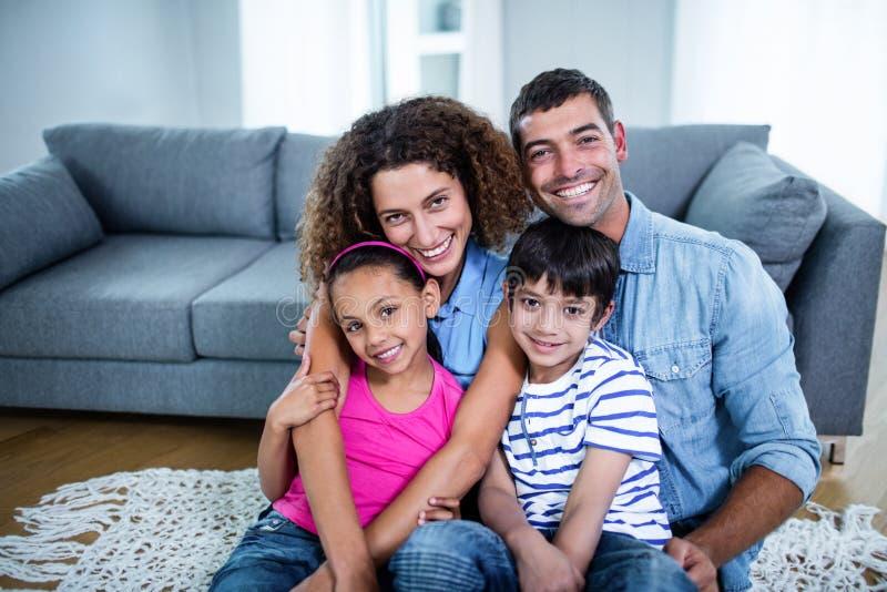 Retrato da família feliz que senta-se junto no assoalho foto de stock royalty free