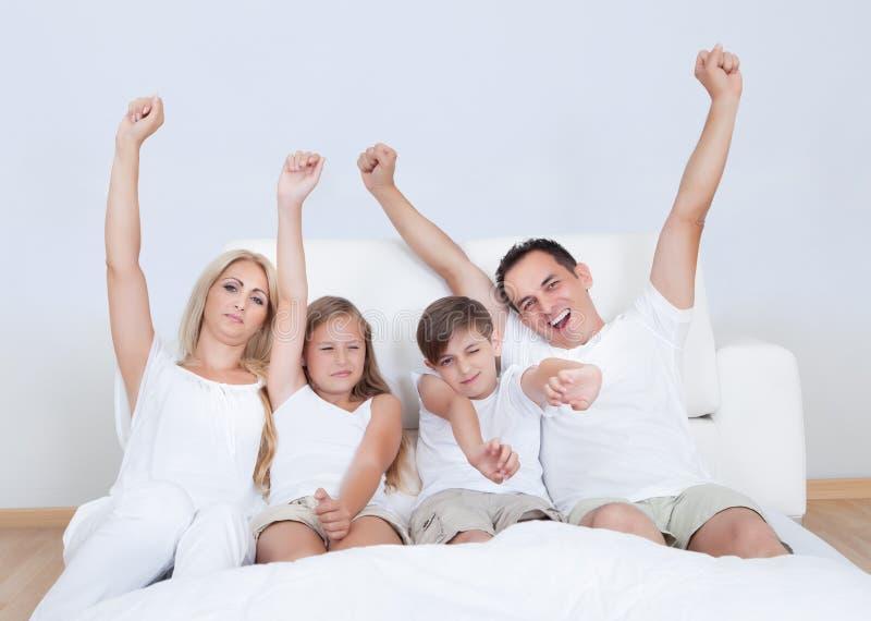 Retrato da família feliz que senta-se na cama imagens de stock royalty free