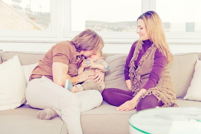 Retrato da família feliz que senta-se no sofá e no jogo fotografia de stock