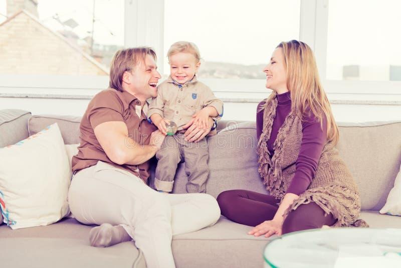 Retrato da família feliz que senta-se no sofá e no jogo imagem de stock