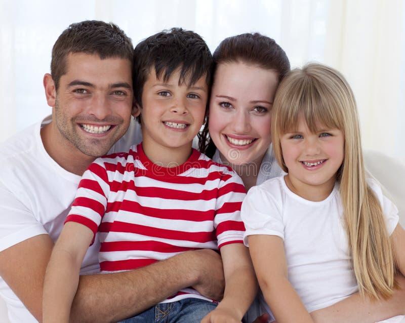 Retrato da família feliz que senta-se no sofá junto foto de stock royalty free