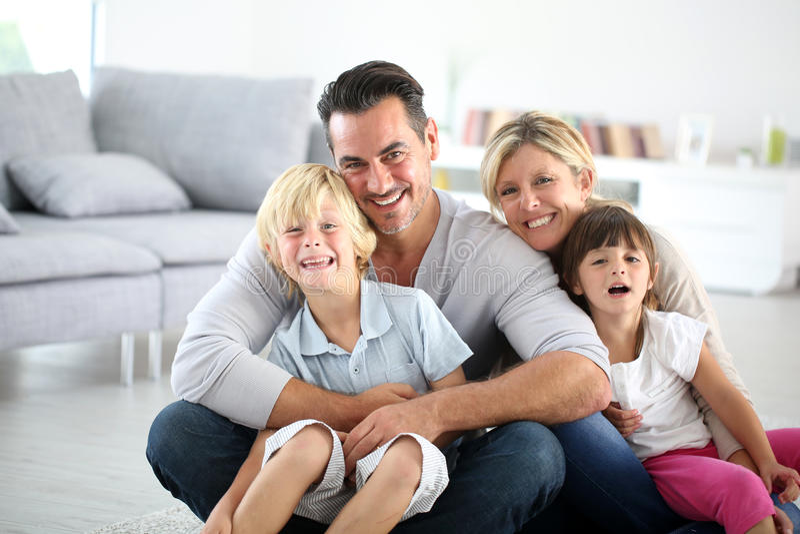 Retrato da família feliz que senta-se para baixo na sala de visitas imagem de stock royalty free