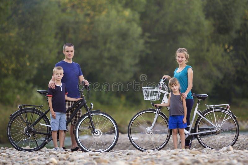 Retrato da família da mãe feliz nova, o pai e duas crianças louras bonitos, menino e menina estando em bicicletas no banco de rio foto de stock royalty free