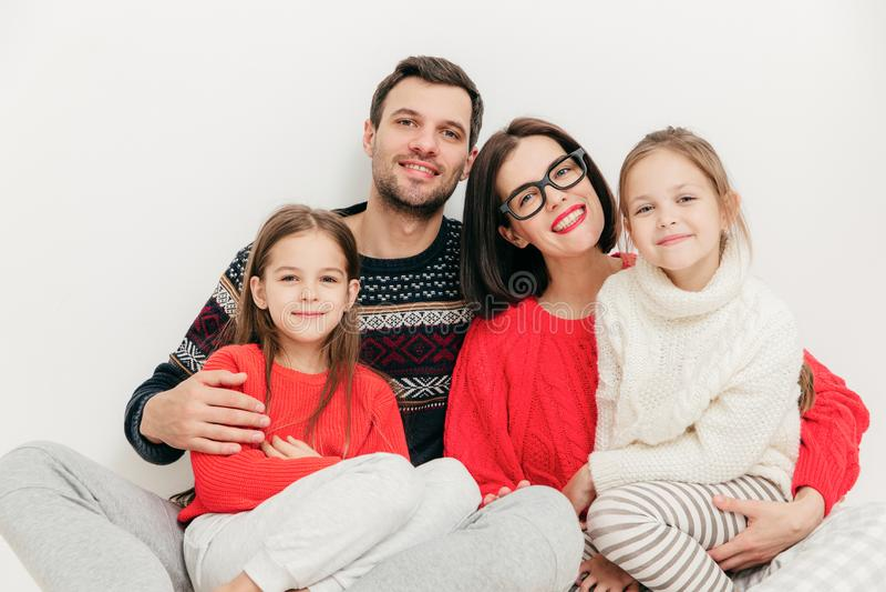 Retrato da família: a mãe, o pai e duas irmãs olham diretamente dentro fotos de stock