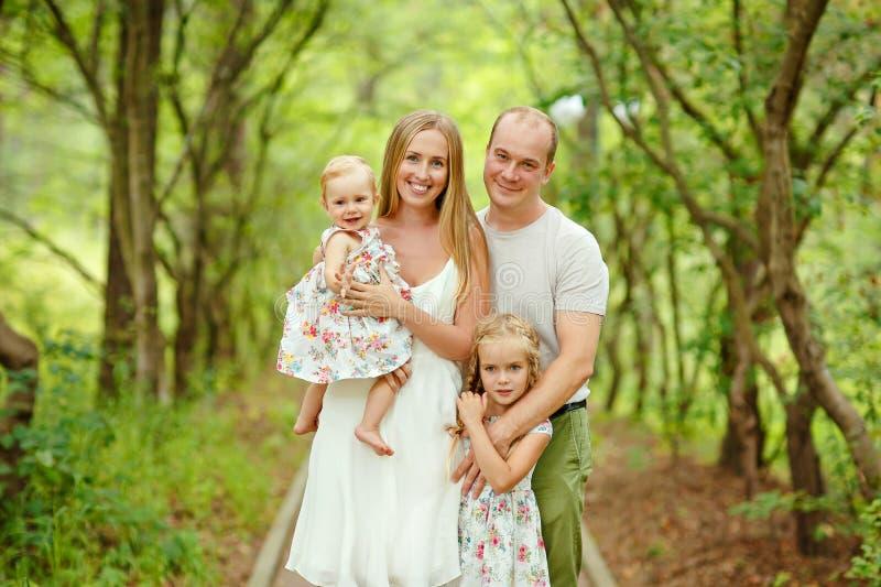 Retrato da família - mãe, pai e louro de duas filhas walkin imagens de stock royalty free