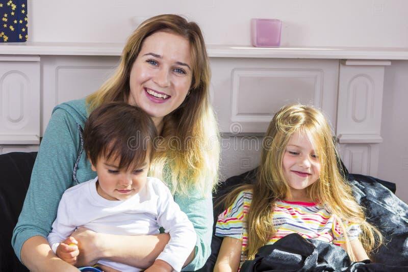 Retrato da família na cama em casa fotos de stock royalty free