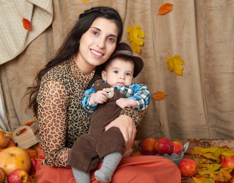 Retrato da família na estação do outono A mulher e o rapaz pequeno sentam-se nas folhas, em maçãs, na abóbora e na decoração amar fotos de stock