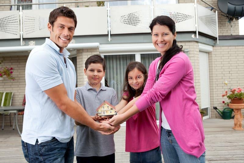 Retrato da família nova com um modelo da casa fotos de stock royalty free