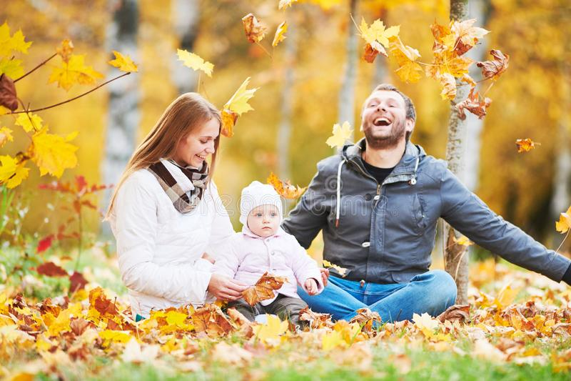 Retrato da família nova feliz com o bebê no parque do outono imagens de stock