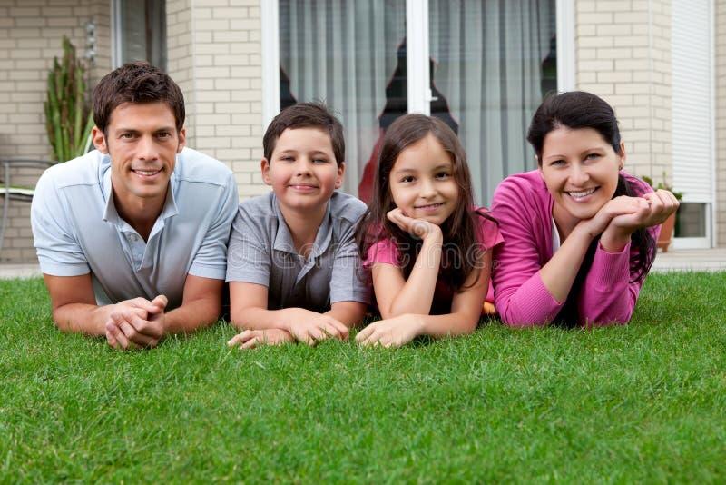 Retrato da família nova feliz que encontra-se na grama fotografia de stock