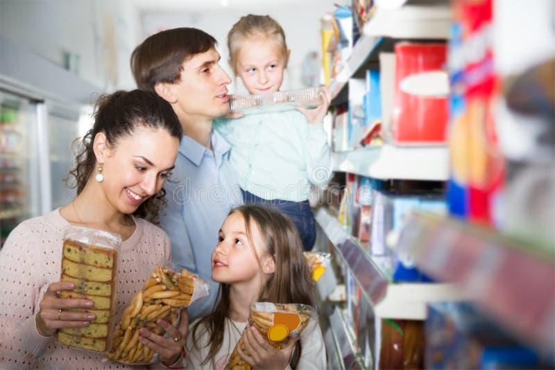 Retrato da família nova no supermercado local imagem de stock royalty free