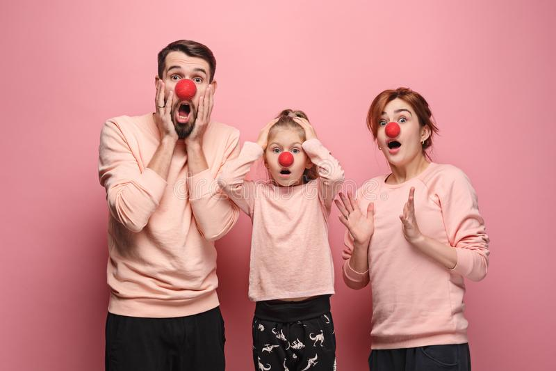 Retrato da família nova que comemora o dia vermelho do nariz no fundo coral foto de stock royalty free