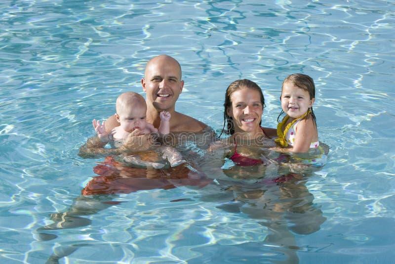 Retrato da família nova que sorri na piscina