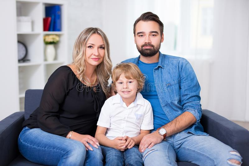 Retrato da família - par e filho pequeno que sentam-se no sofá imagem de stock royalty free