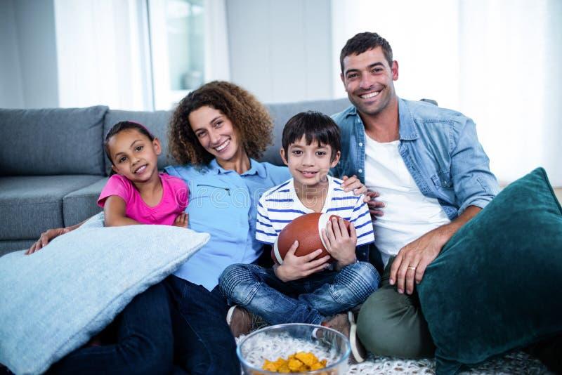 Retrato da família que olha o fósforo de futebol americano na televisão foto de stock royalty free