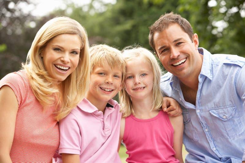 Retrato da família que relaxa no campo imagens de stock royalty free