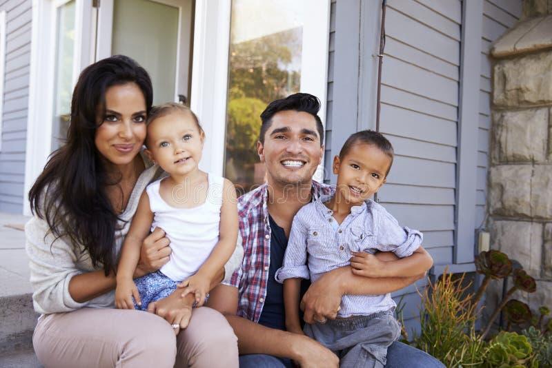 Retrato da família que senta-se em etapas fora da casa imagens de stock