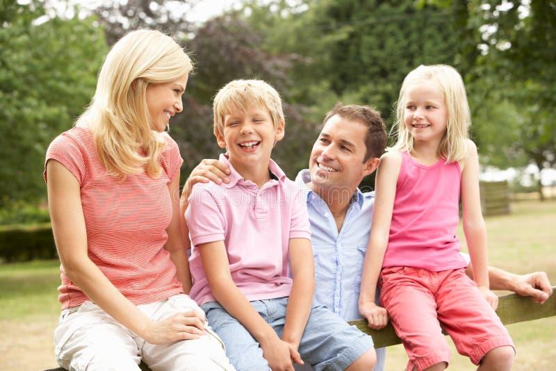 Retrato da família que senta-se na cerca no campo imagens de stock royalty free