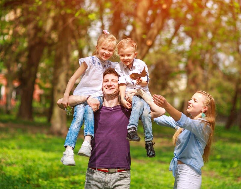 Retrato da família que tem o divertimento no parque de florescência da cidade no dia ensolarado brilhante que passa felizmente se imagens de stock royalty free