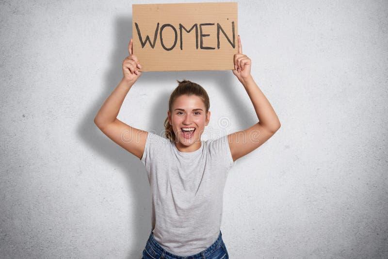 Retrato da feminista bonita encantador que abre sua boca extensamente com felicidade, aumentando os braços, mostrando as mulheres foto de stock