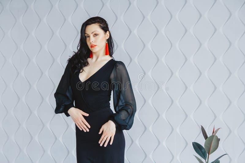 Retrato da forma de uma menina moreno à moda que veste um vestido preto Mulher com o cabelo longo que veste brincos vermelhos Lev fotografia de stock
