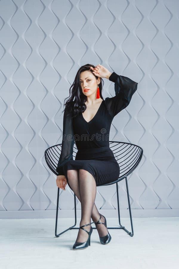 Retrato da forma de uma menina moreno à moda que veste um vestido preto Mulher com o cabelo longo que veste brincos vermelhos mod foto de stock royalty free