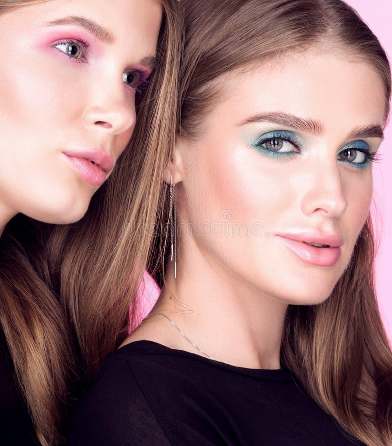 Retrato da forma do close up de duas mulheres bonitas novas no preto Composição brilhante foto de stock royalty free