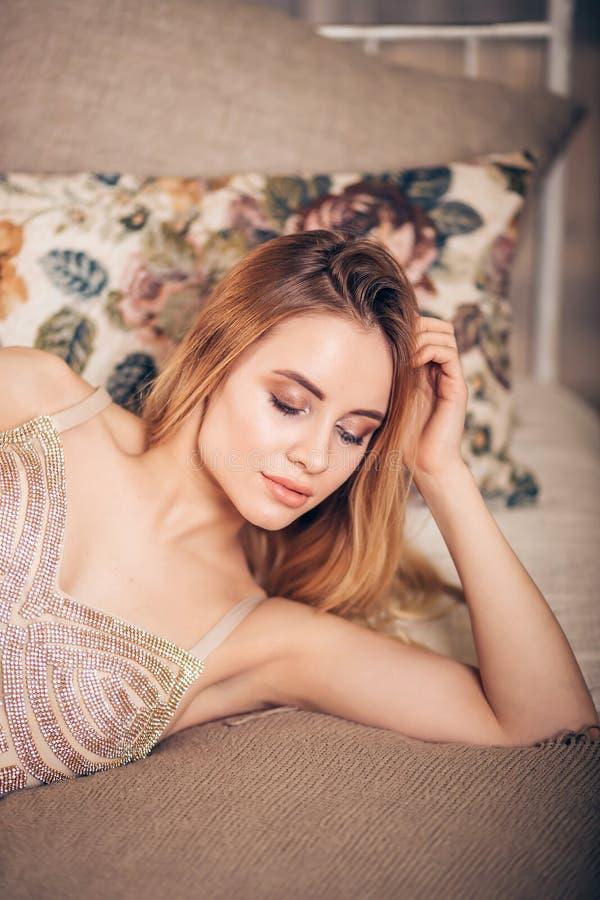 Retrato da forma do close-up da mulher loura 'sexy' bonita no vestido dourado e com composição brilhante e vista para baixo no es imagem de stock royalty free