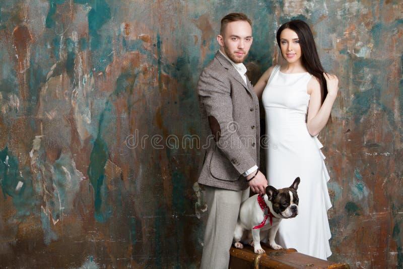 Retrato da forma dos noivos dos pares do casamento com cão e mala de viagem imagem de stock royalty free