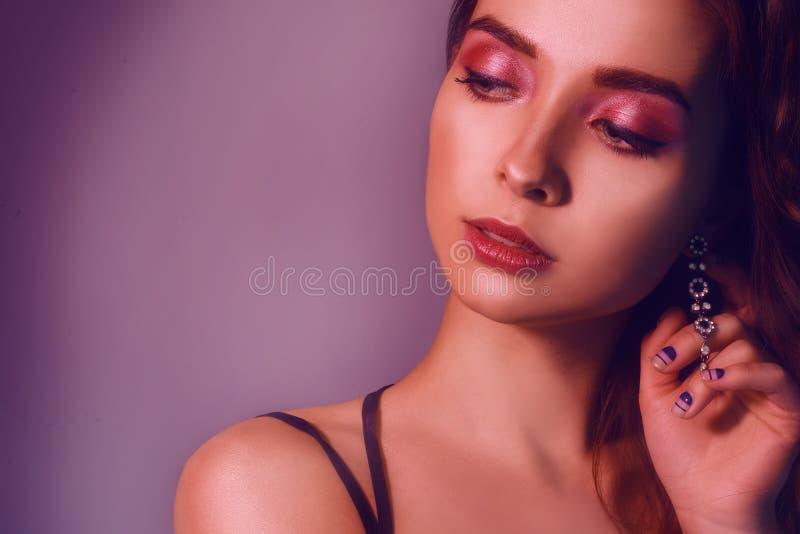 Retrato da forma da menina elegante nova na joia Fundo colorido, tiro do estúdio Mulher triguenha bonita Menina que levanta no né fotografia de stock royalty free