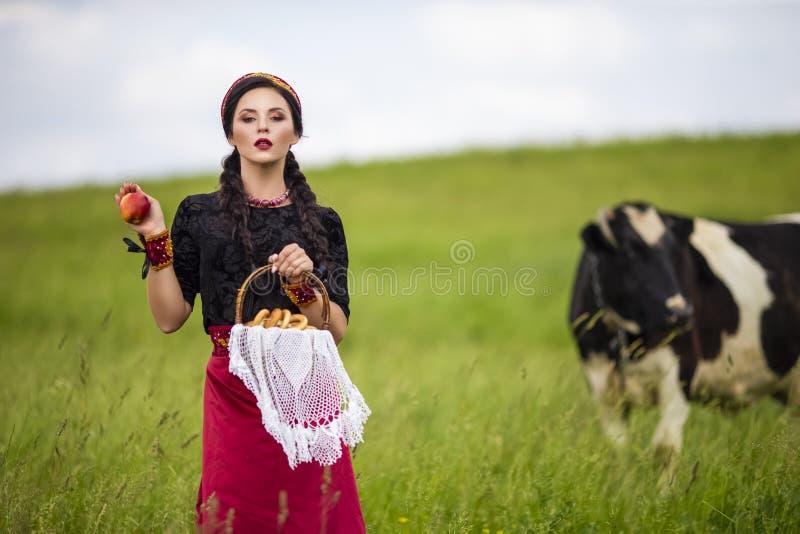 Retrato da forma da morena caucasiano sensual no russo Kokoshnik com a cesta de anéis do pão Levantamento com Apple contra a vaca fotografia de stock